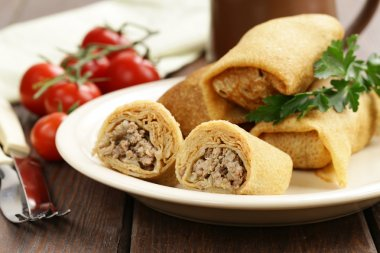 thin pancakes with meat on the plate, Russian cuisine