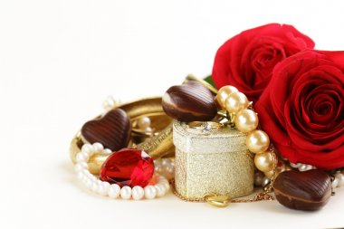 gold jewelry (pearls, necklace, ring) with roses on a white background