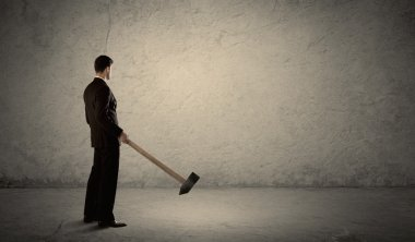 Business man standing in front of a grungy wall with a hammer