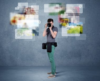 A young professional male photographer holding cameras and taking pictures in front of a blue wall with pictures, icons, text information concept stock vector