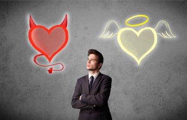 Businessman standing between angel and devil hearts