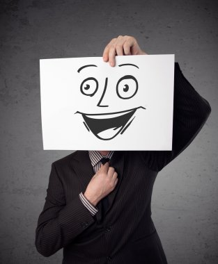 Businessman holding a cardboard with smiley face on it in front