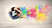 Fotografie Happy teenager jumping with colorful ink splatter on urban backg
