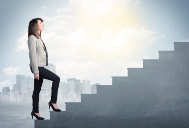 Businesswoman climbing up a concrete staircase concept
