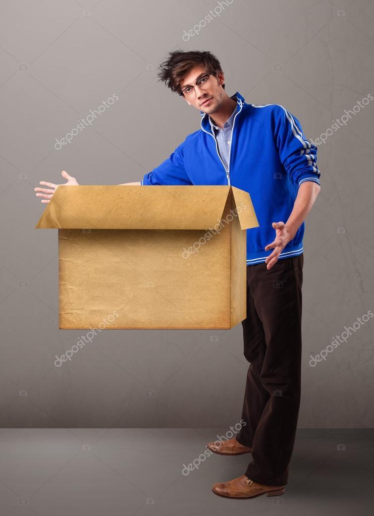 Goog-looking man holding an empty brown cardboard box