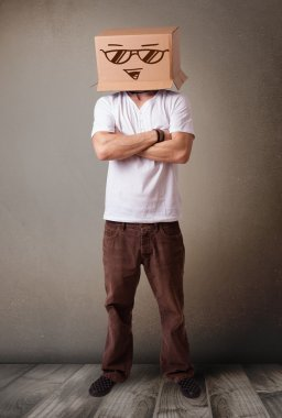 Young man standing and gesturing with a cardboard box on his head with smiley face stock vector