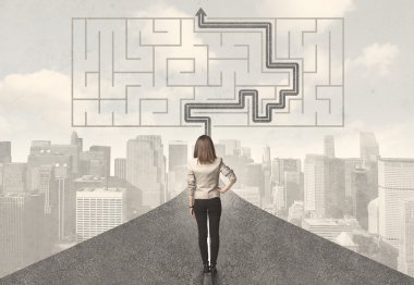Business woman looking at road with maze and solution