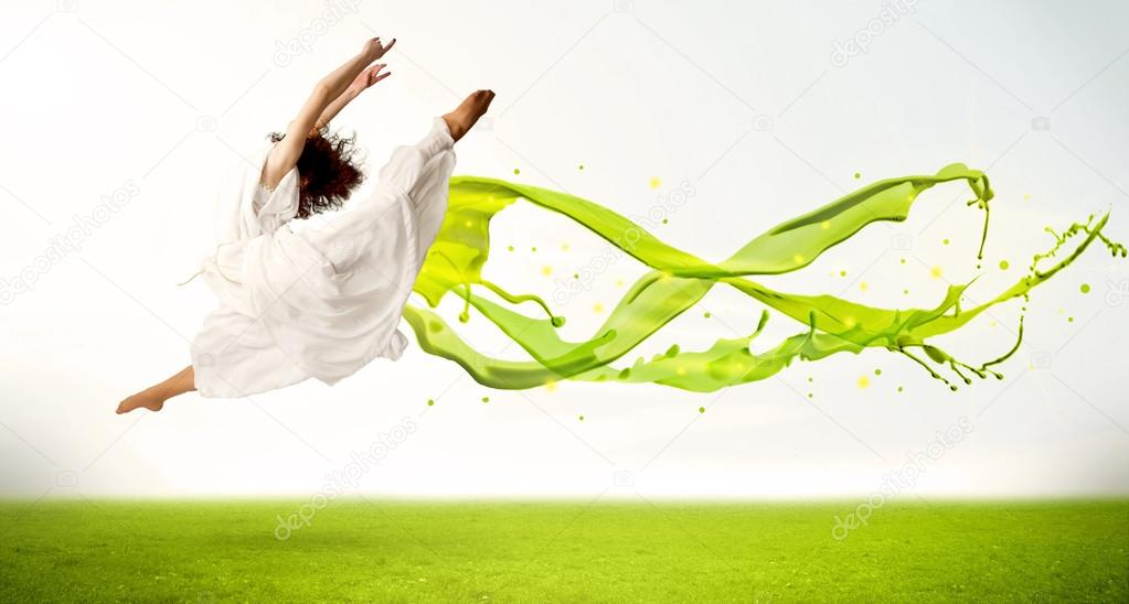 Pretty girl jumping with green abstract liquid dress