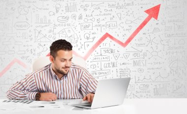 Business man sitting at table with market diagrams
