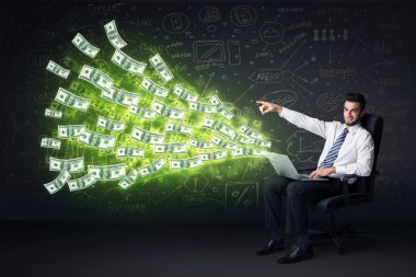 Businessman sitting in chair holding laptop with dollar bills co