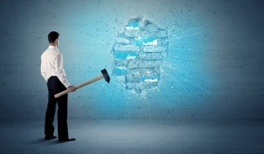 Business man hitting brick wall with huge hammer