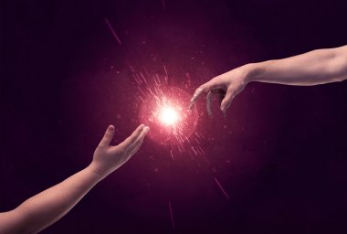 Touching hands light up sparkle in space