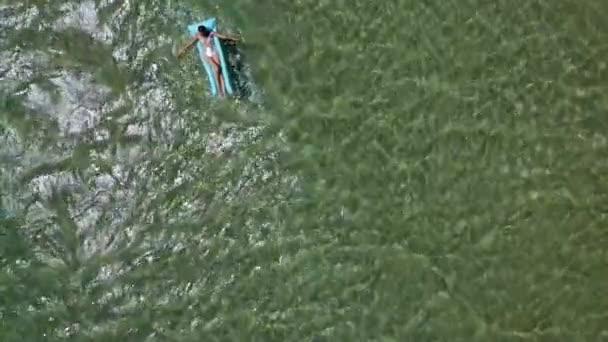 žena leží ve stříbrných plavkách na modré nafukovací matraci v moři