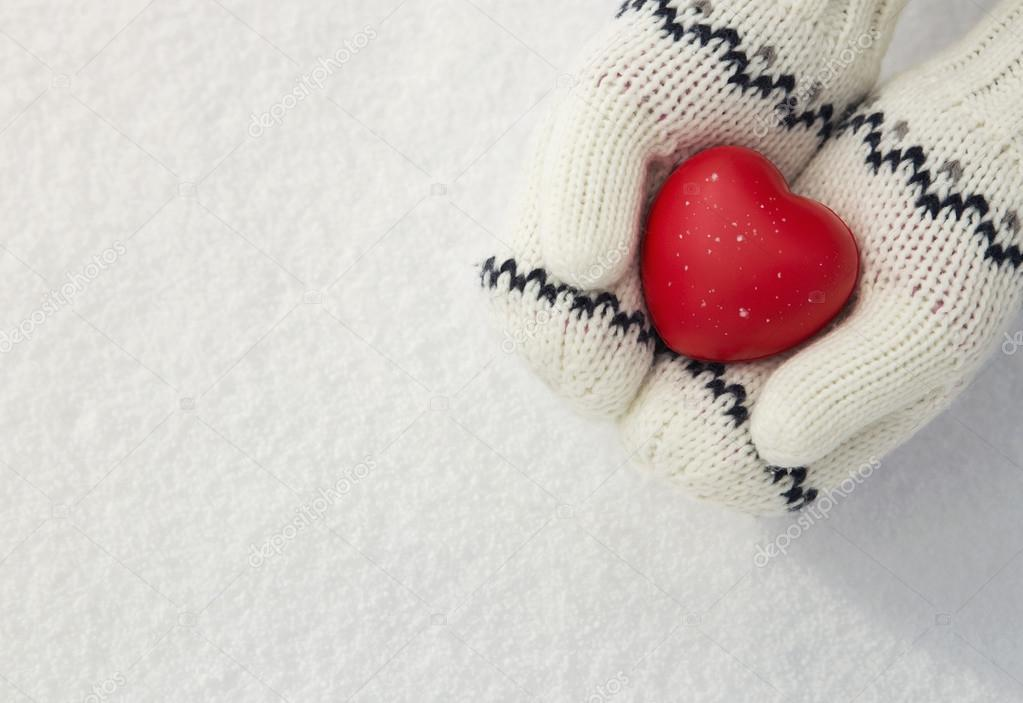 Girl's hands holding red heart in the snow