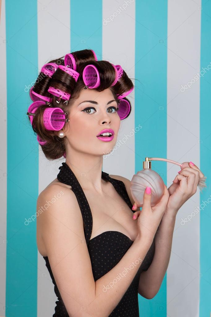 Retro Pin Up Girl Spraying Perfume With Hair Rollers Stock Photo