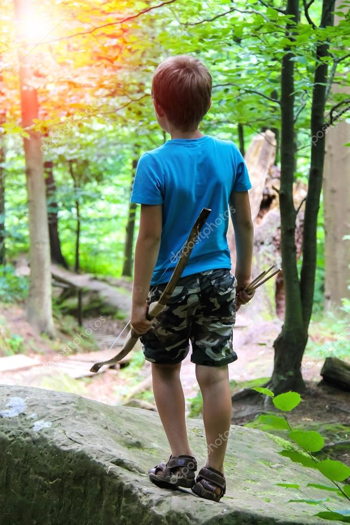 Boy with bow and arrow on a walk in the park.