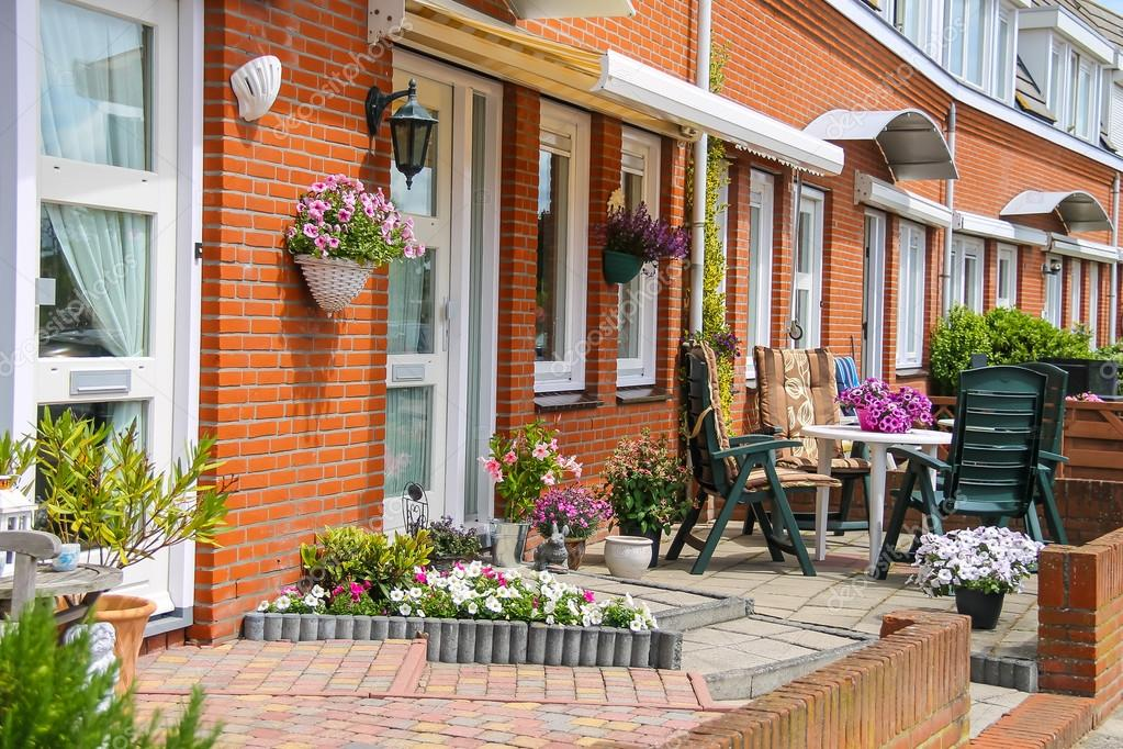 Straatmening van traditioneel huis versierd met planten en meubel