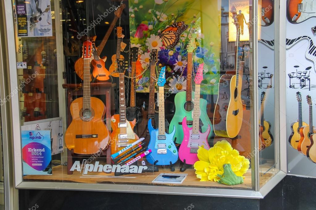 Different types of guitars in the window of the shop of musical