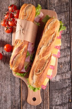 Tasty sandwiches with bacon, salami and vegetables