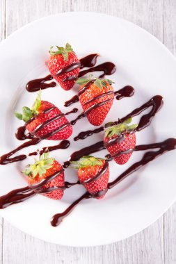 Strawberry in chocolate on plate