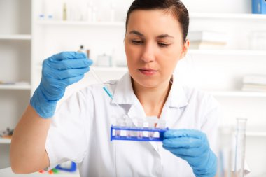 Female Scientist Analyzing Sample In Laboratory.laboratory assistant analyzing a sample.