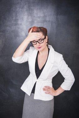 Beautiful teacher with headache on blackboard background
