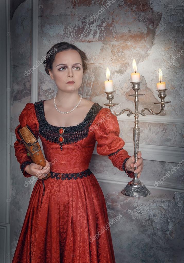2398bbb6dbb1 Giovane e bella donna in abito medievale lungo rosso con candelabro e libro  — Foto di ...