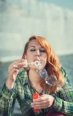 Hipster redhead girl blowing bubbles