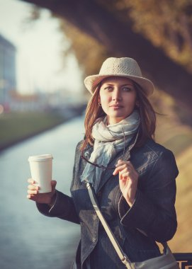 Beautiful young woman in hat and scarf with cup of coffee