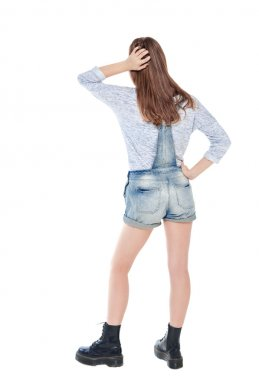 Young teenage girl standing and looking on something. Back pose,