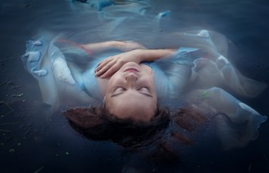 Young beautiful drowned woman in blue dress lying in the water