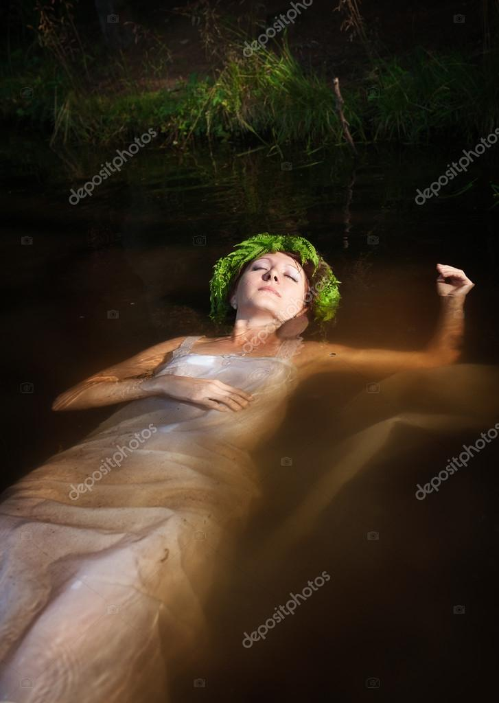 Beautiful drowned woman with fern wreath lying in the water