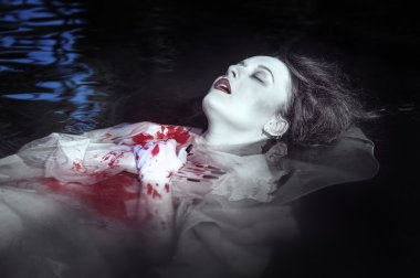 Young beautiful drowned woman in bloody dress
