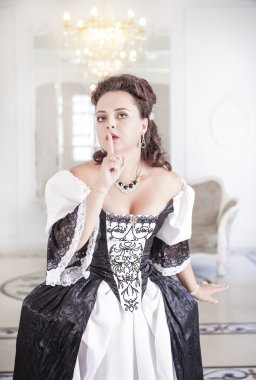 Young beautiful medieval woman in dress making silence gesture