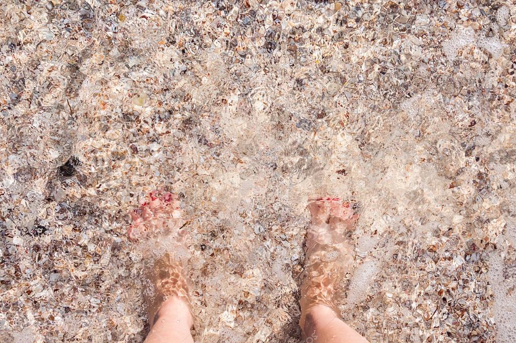 Feet in the sea on a sandy beach