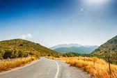 Strada tra le montagne e i boschi di ulivi