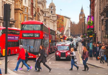 Iconic red double decker bus and cars on the street in London