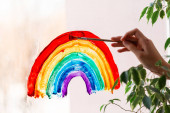 Little girl painting rainbow on window during Covid-19 quarantine at home. Stay at home social media campaign for coronavirus prevention, lets all be well, catch the rainbow
