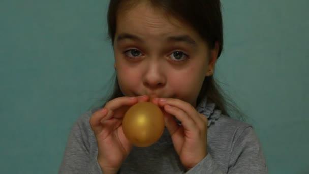 lustiges und glückliches Mädchen beim Versuch, den Ball aufzublasen