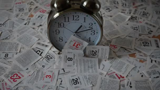 The falling leaves of the calendar tear-off calendar and a large clock