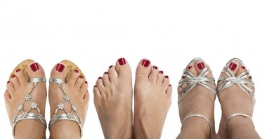 Three pairs of women's feet in silver sandals and barefoot on a white background.The view from the top.
