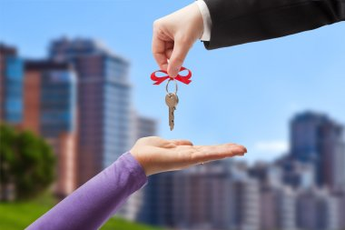 Handing the keys to the new owner on the background of the urban landscape