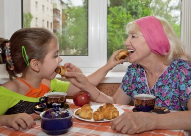 Fun tea party. Grandmother with granddaughter feed each other croissants.