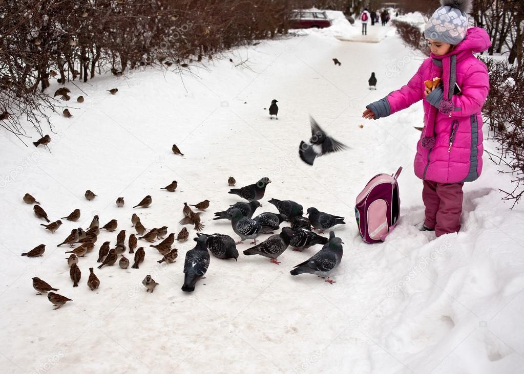 School girl feeding birds in winter