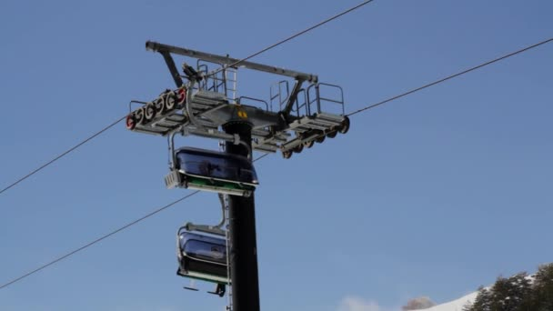 Skiers ride chairlift up towards top of volcano mountain etna