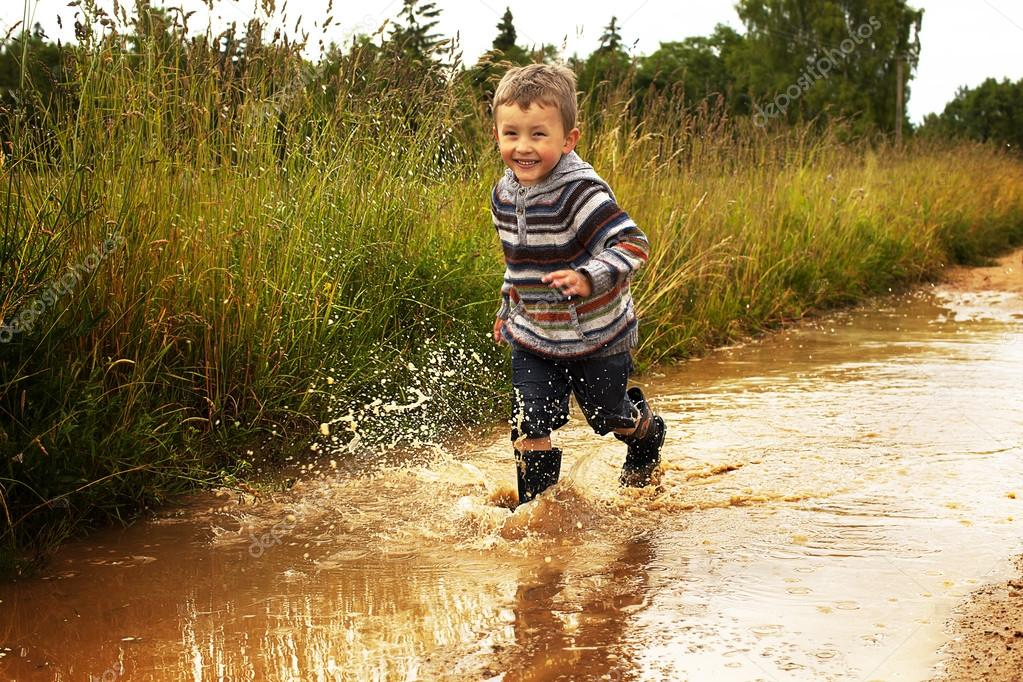 kid playing in puddle