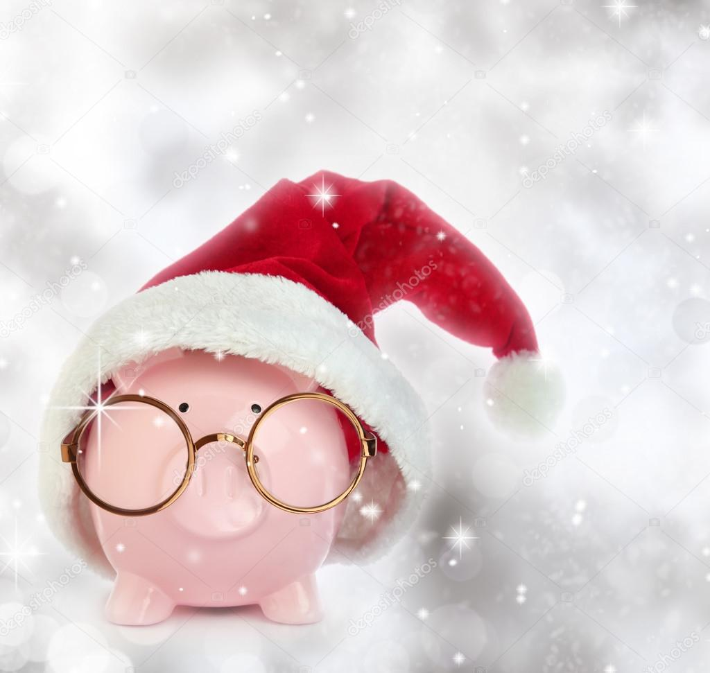 Piggy bank with Santa Claus hat and eyeglasses in a glittery background