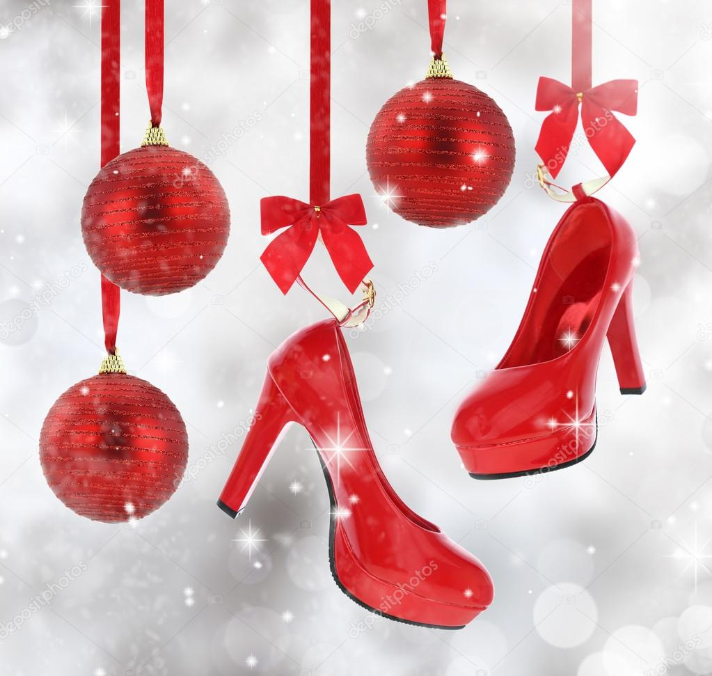 High heels shoes and Christmas balls hanging on red ribbon