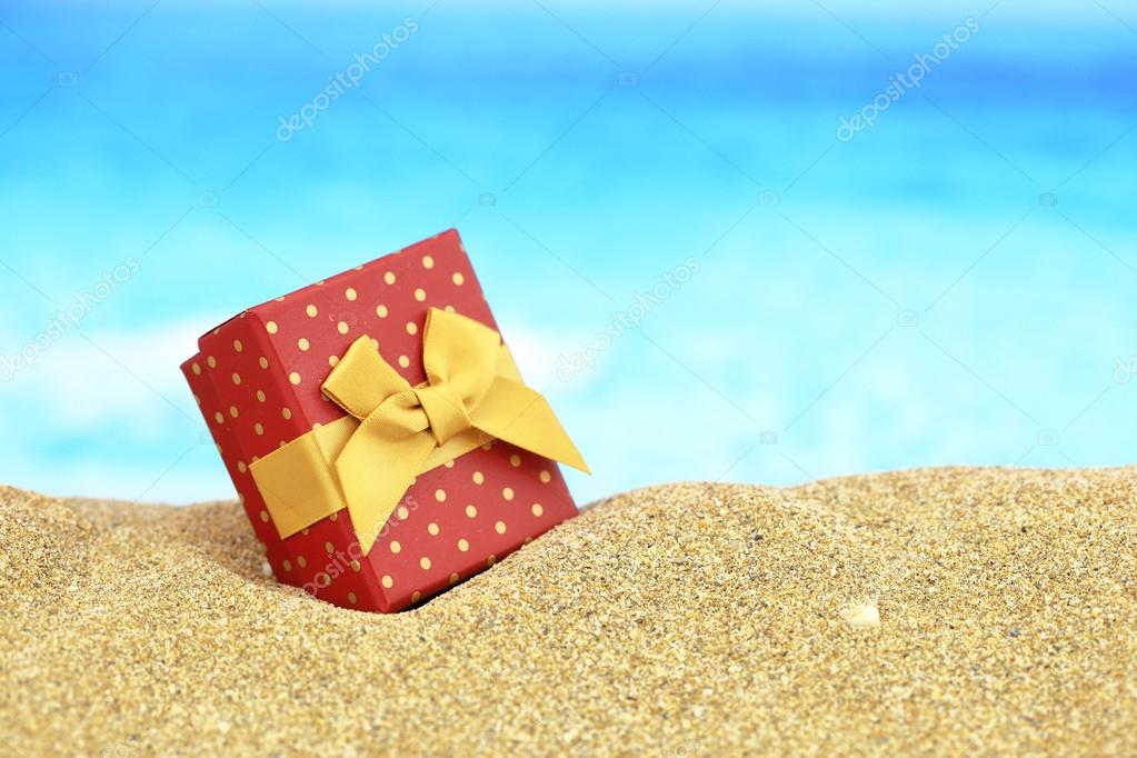 Gift box with bow on the sand