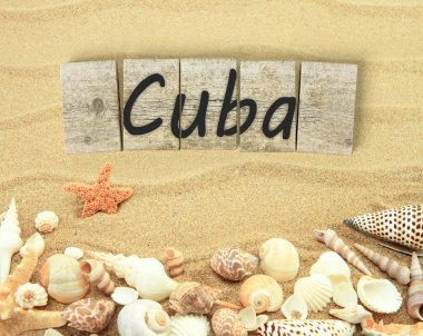 Cuba on wooden board pieces with sea shells and sand